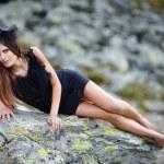 Elegant woman laying on the mountain rocks — Stock Photo