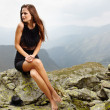 Elegant woman in dress sitting on the rocks — Foto Stock