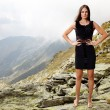 Elegant lady in dress standing on the mountain rocks — Stock Photo #32086833