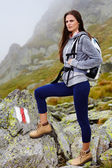 Woman hiker standing on the mountain rocks — Stock Photo