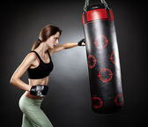 Woman hitting the punching bag — Stock Photo
