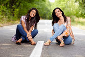 Mother and daughter sitting cross legged on the road — Stock Photo