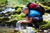Tourist washing hands in a river — Stock Photo
