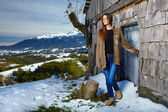 Young beautiful woman getting out from a cabin log in — Stock Photo