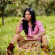 Sexy brunette near a basket of apples — Stock Photo