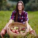 Beautiful woman sitting near a basket of apples — Stock Photo