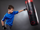 Boy hitting the punching bag — Stock Photo
