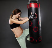 Athletic woman kicking the punching bag — Stock Photo