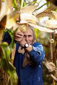 Old female farmer at corn harvest — Stock Photo