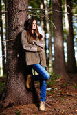 Woman leaning on a tree — Stock Photo