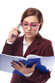 Teacher checking the class book and talking to the phone — Stock Photo