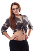 Sexy woman wearing sunglasses, army shirt and standing akimbo — Stock Photo