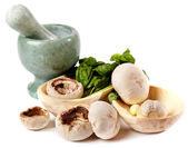 Fresh champignons, garlic and basil in wooden bowls near a morta — Stock Photo