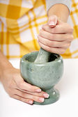 Crushing the garlic in a granite mortar — Stock Photo