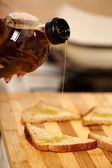 Cook's hand holding a bottle of olive oil and pouring it over sliced toasted bread — Stock Photo