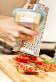 Cook's hands grating parmesan over tomato bruschettas — Stock Photo