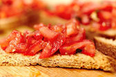 Tomato bruschetta on a wooden board — Stock Photo