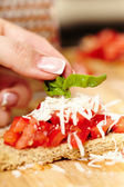 Decorating the tomato bruschettas with basil — Stock Photo