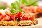 Italian tomato bruschettas decorated with basil and parmesan — Stock Photo