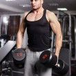 Athletic man holding heavy dumbbells — Stock Photo