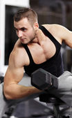 Athletic man working with heavy dumbbells — Stock Photo