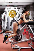 Sexy brunette working her bottom at the gym — Stock Photo