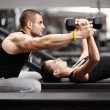 Stock Photo: Personal trainer helping womat gym