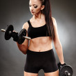 Athletic woman working out with dumbbells — Stock Photo #38044957