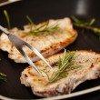 Fried pork chops in the frying pan decorated with rosemary — Stock Photo