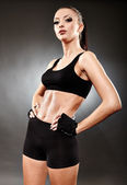 Athletic woman in sportswear standing akimbo — Stock Photo