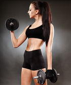 Athletic woman working out with dumbbells — Stock Photo