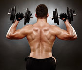 Athletic young man working with heavy dumbbells — Stock Photo