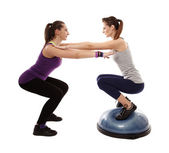 Woman doing squats on a bosu ball, helped by the peronal trainer — Stock Photo
