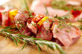 Spit of spiced raw pork meat with pepper on a wooden board — Stock Photo
