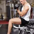 Handsome man working with heavy dumbbells in the gym — Stock Photo