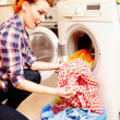 Housewife putting the laundry into the washing machine — Stock Photo #38121489