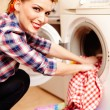 Housewife putting the laundry into the washing machine — Stock Photo