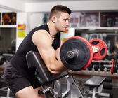 Athletic man working his arms at the preacher curl bench — Stock Photo