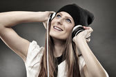 Woman listening to music at headphones — Stock Photo