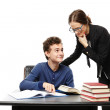 Teacher standing next to the student's desk and the student pointing the teacher something in the book — Stock Photo #38377217
