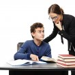 Teacher standing next to the student's desk and the student pointing the teacher something in the book — Stock Photo #38377225