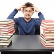 Angry stressed student sitting at his desk with hands on the head between two piles of books — Stock Photo