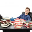 Student having a rest with the legs on the desk, daydreaming among piles of books — Stock Photo #38377289