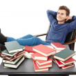 Student having a rest with the legs on the desk, daydreaming among piles of books — Stock Photo #38377313