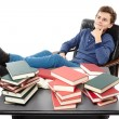 Student having a rest with the legs on the desk, daydreaming among piles of books — Stock Photo #38377345