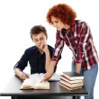 Stock Photo: Mother standing near son's desk helping him doing his homework