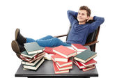 Student having a rest with the legs on the desk, daydreaming among piles of books — Stock Photo