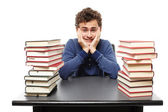 Overwhelmed student with face in hands sitting at his desk between two piles of books — Stock Photo