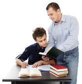 Father standing near son's desk helping him doing his homework — Stock Photo