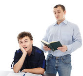 Teenager sitting at his desk showing boredom while his father is — Stock Photo